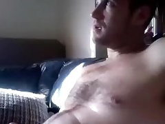 Dishy guy is having fun at home and filming himself on computer webcam